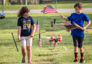 Local scouts honor veterans with flags in cemetery