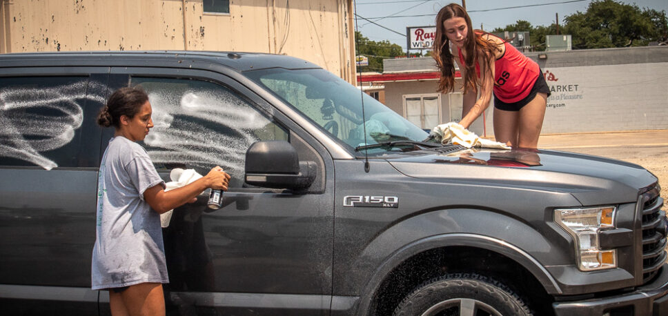 BHS Varsity Cheerleaders brave hot temperatures for car wash fundraiser